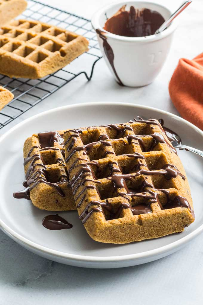 Side view of Grain-Free Pumpkin Chocolate Chip Waffles on a plate with waffles on a cooling rack and a dish of melted chocolate in the background.