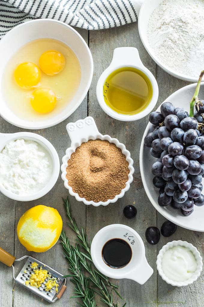 Overhead view of ingredients for Rosemary Grape Ricotta Cake arranged on a wooden surface.