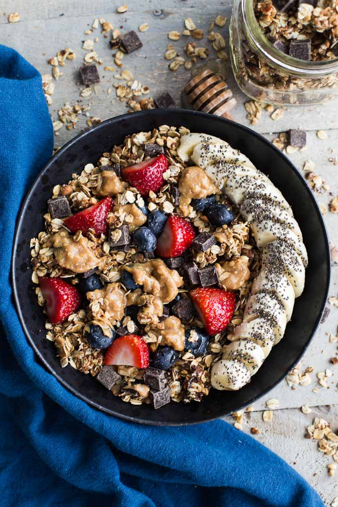 Overhead view of Dark Chocolate Peanut Butter Granola in a black bowl surrounded by a blue napkin.