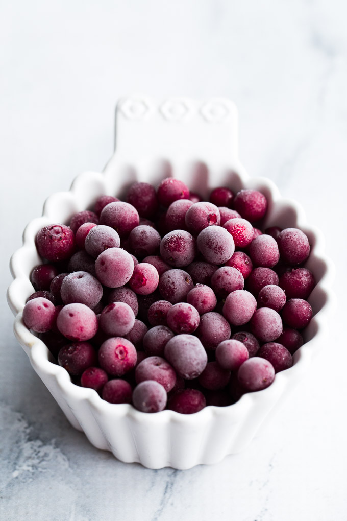 Up-close view of a cup of frozen partridgeberries.
