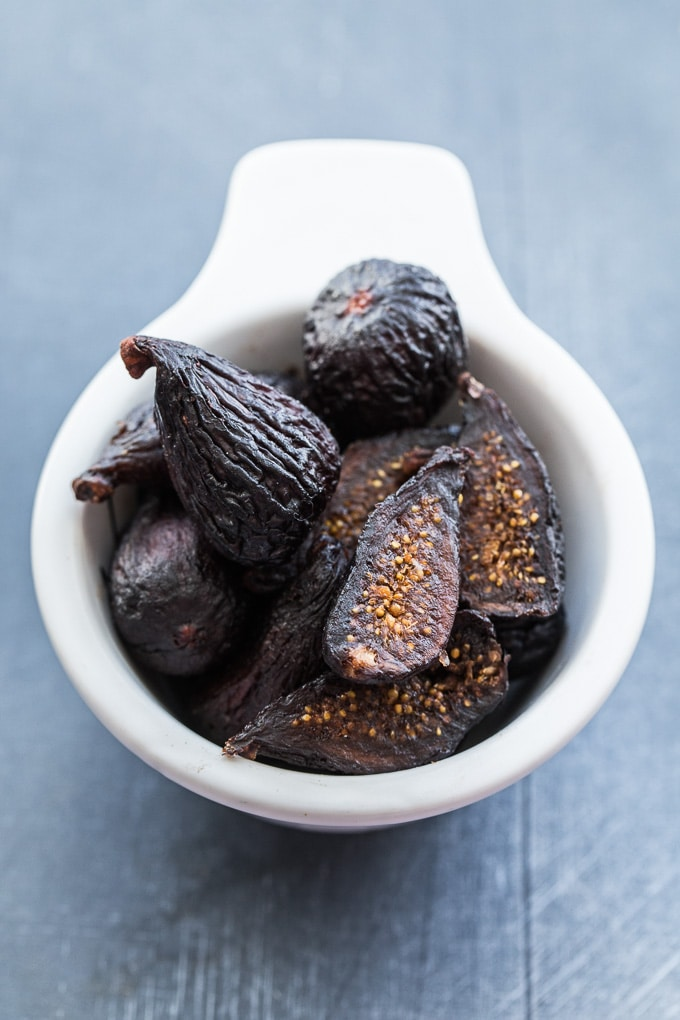 Dried mission figs in a white cup on a dark surface.
