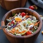Winter Citrus Crunch Salad in wooden bowls on a dark surface.