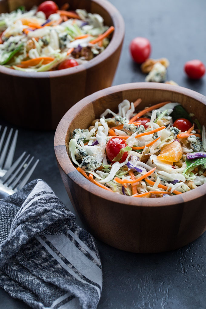 Side view of Winter Citrus Crunch Salad in wooden bowls on a dark surface.