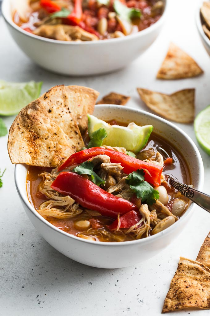 Up-close view of Chicken Fajita Soup in a white bowl on a white surface.