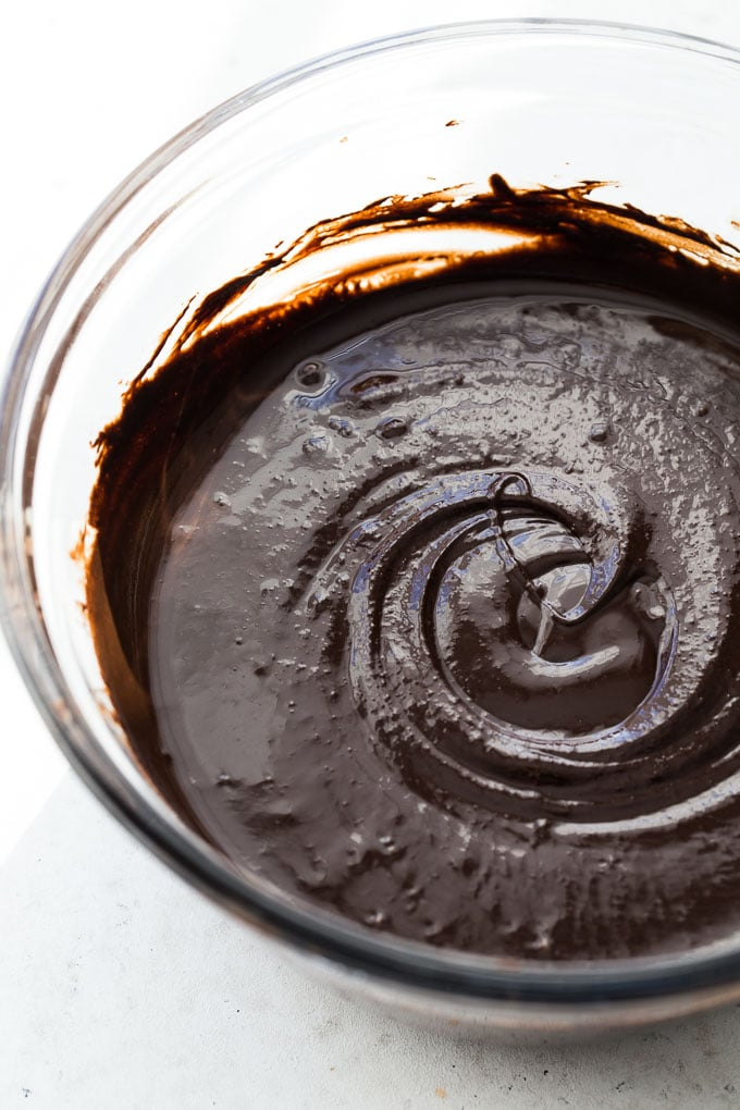 Up-close view of melted dark chocolate and tahini in a glass bowl.
