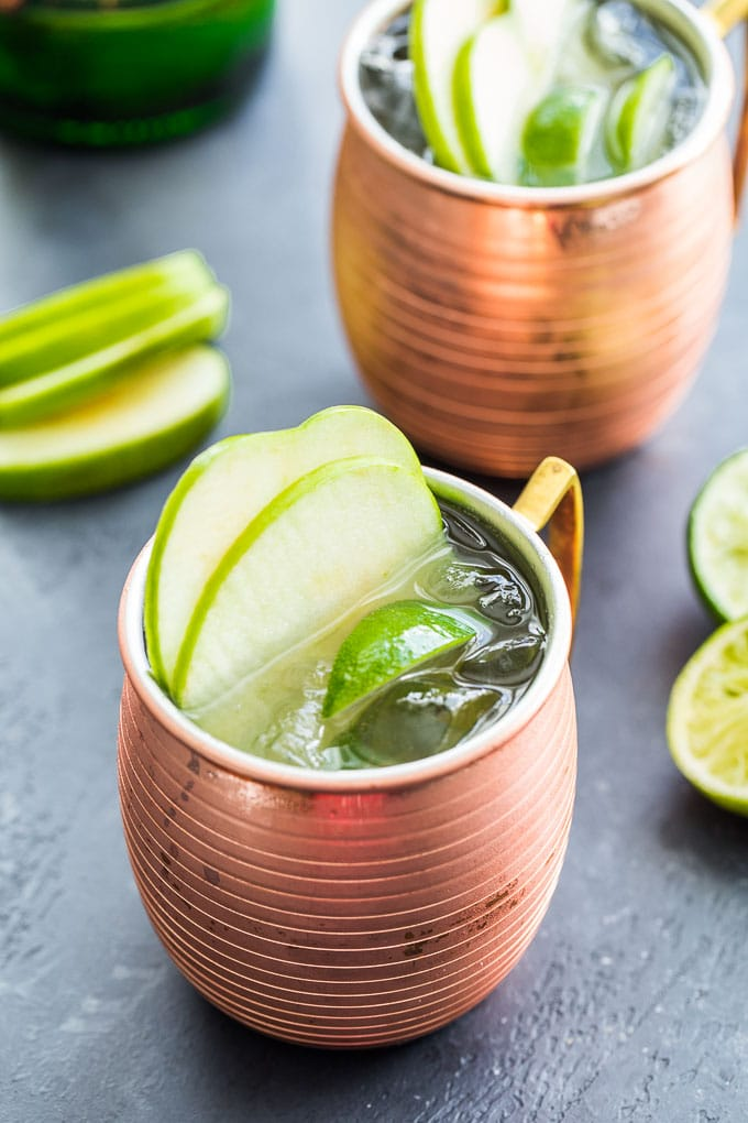 Up-close view of two Green Apple Irish Mules in copper mugs on a dark surface.