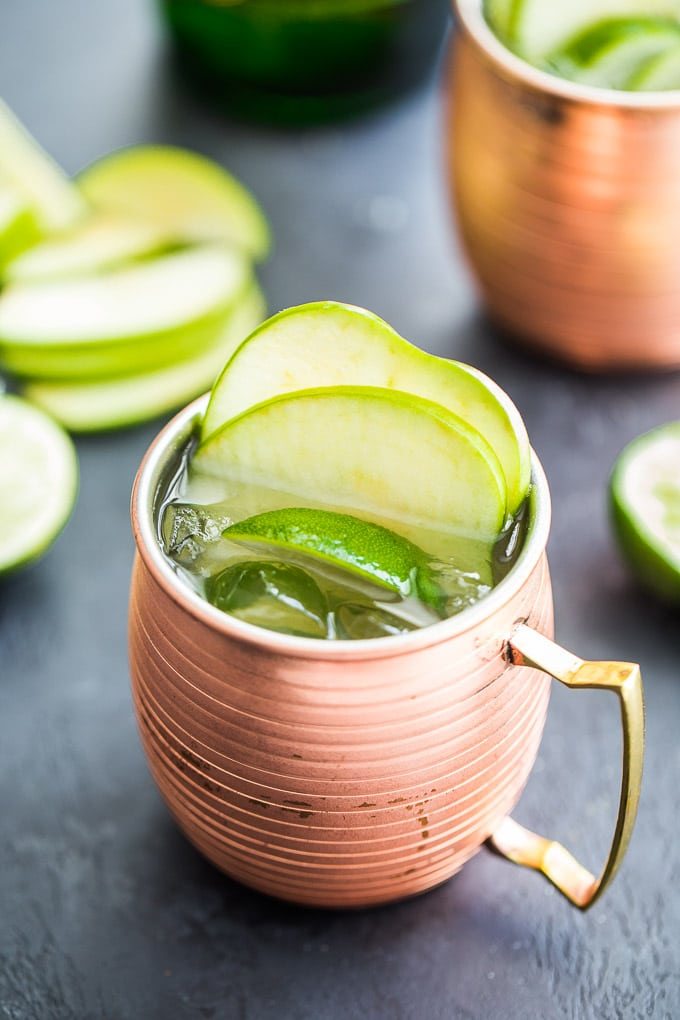 Up-close view of a Green Apple Irish Mule in a copper mug on a dark surface.