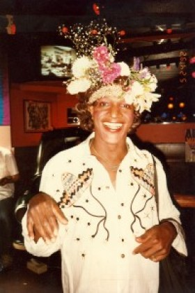 """A picture of a smiling, decadently beautiful flower arrangement hat wearing Marsha """"Pay It No Mind"""" Johnson"""