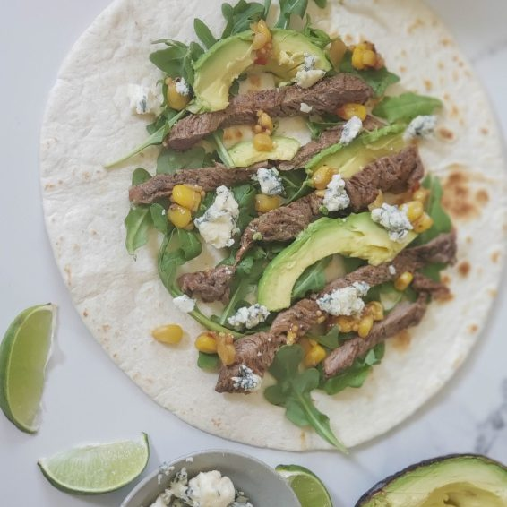 Carne Asada and bleu cheese soft tacos with arugula, avocado, and corn relish
