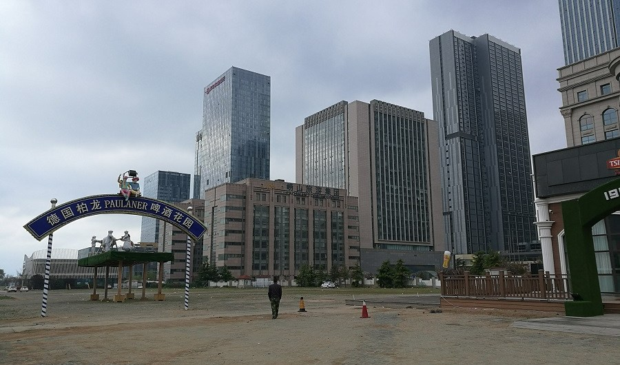 A man walks towards skyscrapers in Qingdao, China.