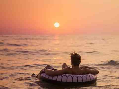 faceless male traveler in inflatable ring on ocean admiring sunset