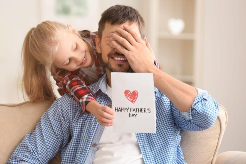 Girl giving father a handmade card