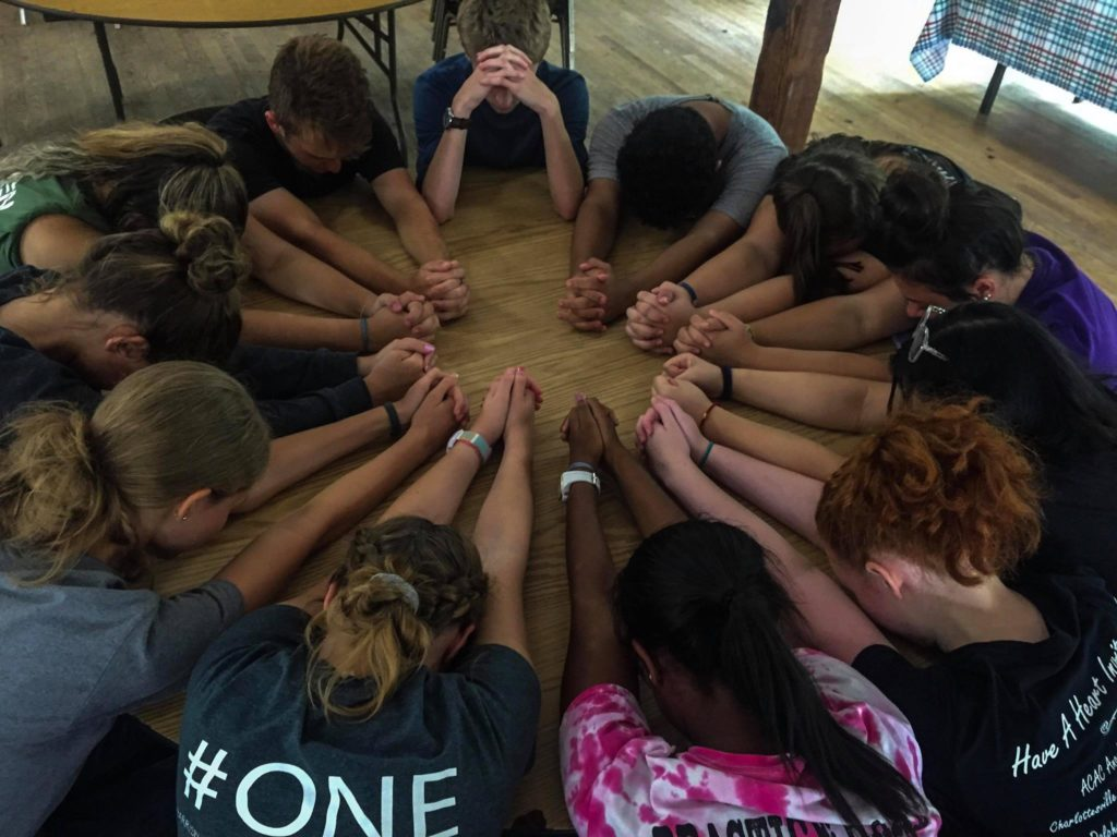 Harrisburg Christian School kids praying at table with hands in a circle