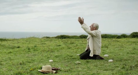 Sherlock Holms (Ian McKellen) kneels in the middle of his memorial stones, raising his arms skyward.