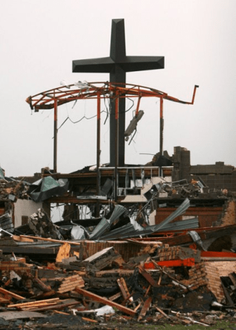 A large cross stands straight among the rubble of a Joplin church.