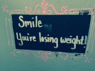 """Smile...You're losing weight!"" Chalk board sign on green door with pink swirl borders"