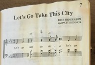 "The first line in the sheet music, coffee stained, of ""Let's Go Take This City."""