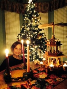 A little girl smiles through lit Advent candles with a bright Christmas tree shining behind her and a lit nativity carousal next to her.