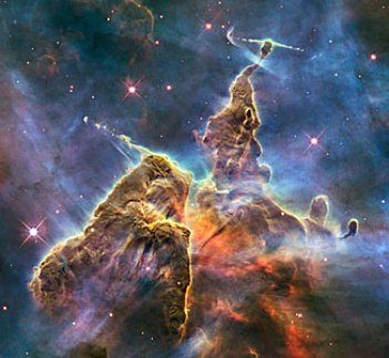 Fantasy-like this star formation looks like a moving, jagged mountain of brown, orange, aqua, and purple. The hazy dark blue background sparkles with pricks of purple light