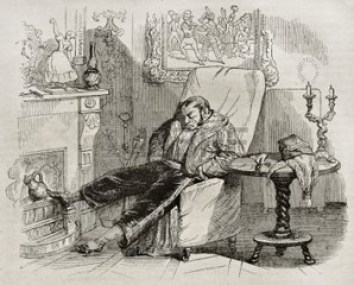 Man sleeping in an armchair by fireplace