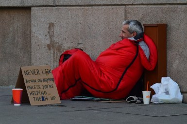 "Cardboard sign by homeless man in red sleeping bag says, ""Never look down on anyone unless you're helping them up."""