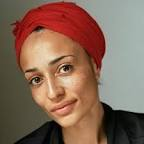 Zadie Smith is of African descent with light, brown skin, an oval face, dark and kind black eyes, manicured eyebrows, and closed smiling lips. She looks directly into the camera, wearing a red head scarf and a black shirt.