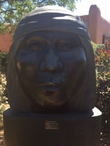 "A 49""x42""x42"" bronze head of an Apache man, sober, shoulder-length hair topped with a head scarf"
