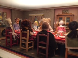 Eight little dolls sit on chairs at a table ladened with goodies for Victorian tea.