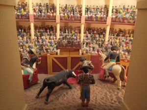 Hundreds of little clay people sit in bleachers in an arena. The bull fighter and bull with two Spaniards on horse back are in the front.
