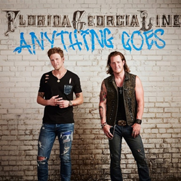 "The singing duo stand in front of a white brick wall with Florida Georgia Line printed on wall in black letters and ""Anything Goes"" looking like graffiti in blue letters."