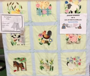 A white ribbon hangs on this baby quilt of light green and white border with farm animals appliquéd in pastel colors on each of the nine squares.