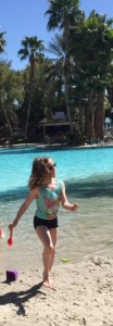 Eight-year-old girl is in sand along a tropical pool with palm trees.