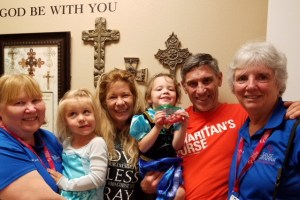"Two blue-shirt women and a man in orange shirt flank a smiling blond-hair grandma with two little girls dressed in princess customs. Behind them are a wall of crosses and the words ""God Be With You."""