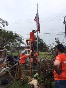 An orange shirted man holds a ladder while another man stands on it and adjusts a raised American flag and pole.