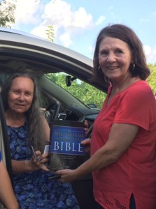 Woman sitting in car touches a Bible that another woman, standing by her, is holding. Both are smiling.