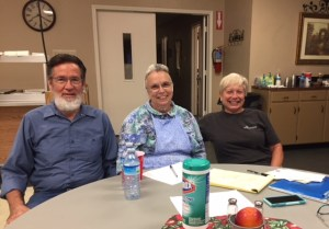 A bearded man, woman in apron and cap, and another woman in grey t-shirt sit at a round table smiling.