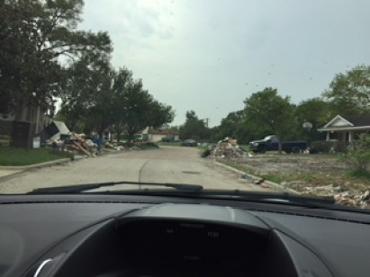 A photo from car showing a street lined with lots of discarded household items and garbage that was flood-damaged.