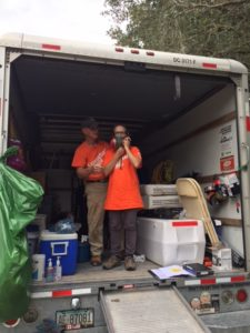 Standing inside a U-haul, an orange shirted man is helping an orange-shirted woman adjust her mask.