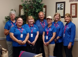 A posed shot of six women and one man in the center, all in blue shirts with red lanyards and ids.