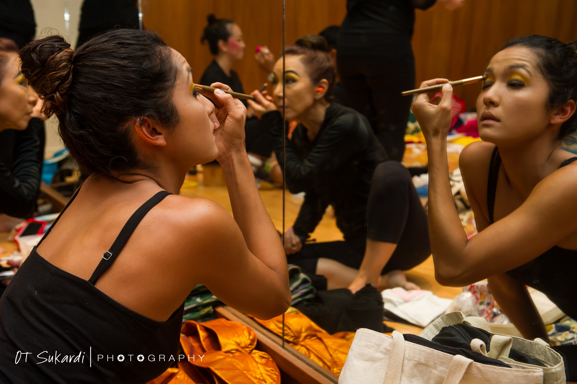 Performer does makeup in mirror