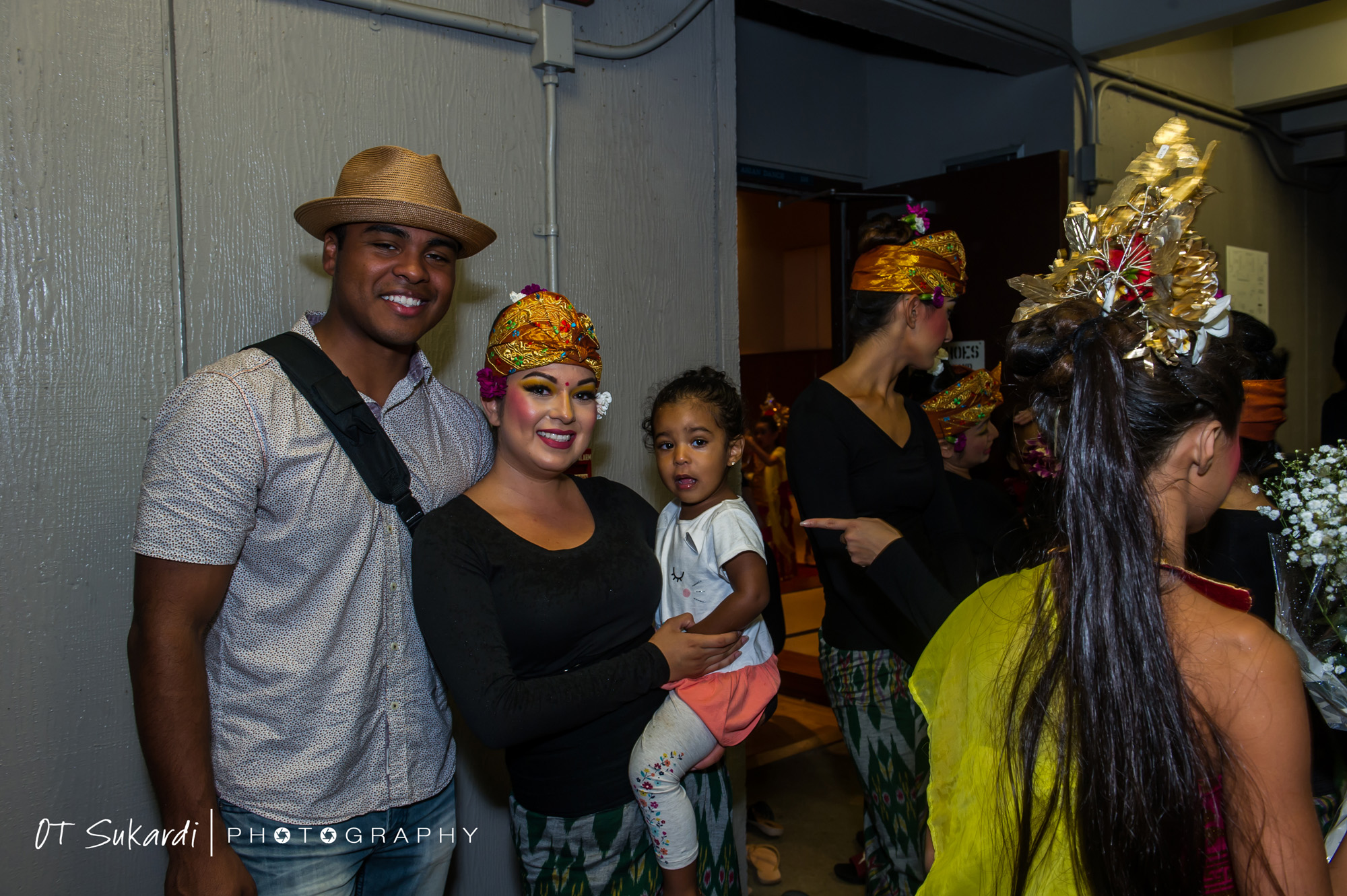 smiling man and woman (in costume) holding child after show