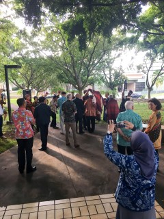 Crowd gathers in courtyard before garden blessing ceremony