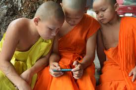 3 boys dressed in monks robes playing video games on a smart phone.