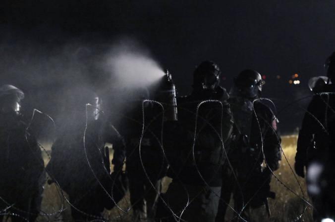 Police spraying mace - photo by Liz George
