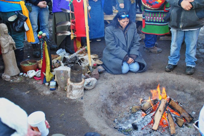Activists offering thanks of sage, fir nettles, and tobacco to the sacred fire - photo by C.S. Hagen