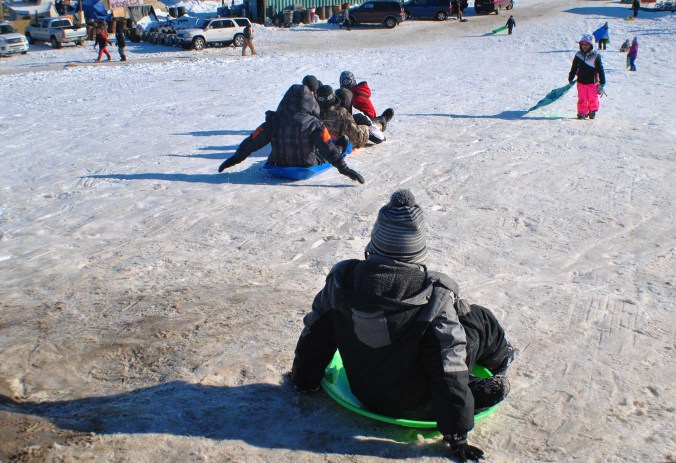 Children sledding down Media Hill - photo by C.S. Hagen