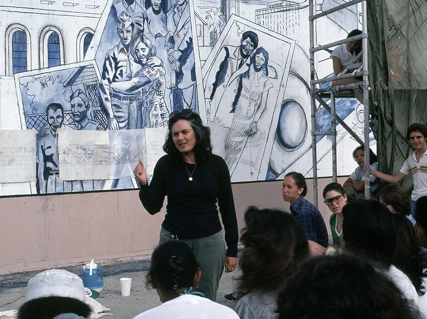 Judy Baca standing in front of mural