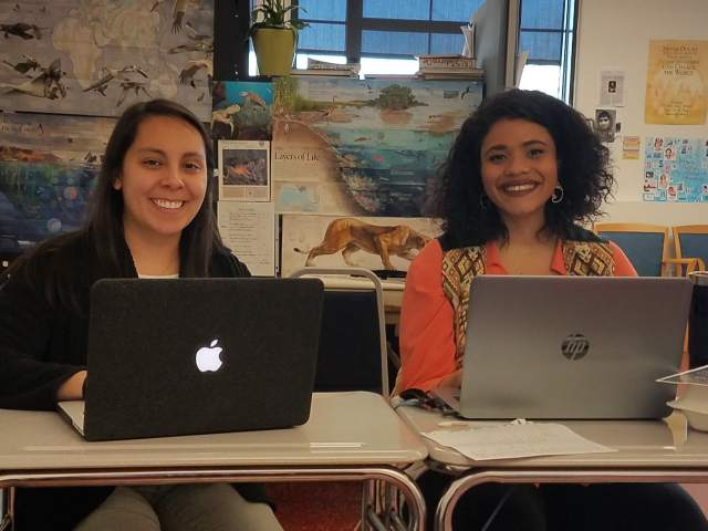 Two young women seated at laptops looking at the camera, one is a Latinx woman in a black sweater and the other is an African-American woman in an orange shirt and patterned vest.