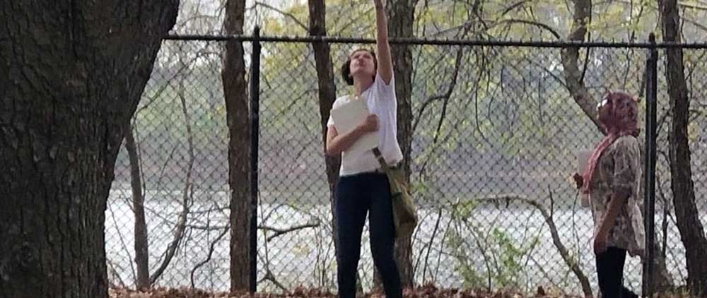 In the background a fence and beyond that, a body of watr. Light skinned adult woman carrying notebook stretches up to point toward the treetops. Water is in the background. A dark-skinned student wearing a hijab looks upward where the adult is pointing