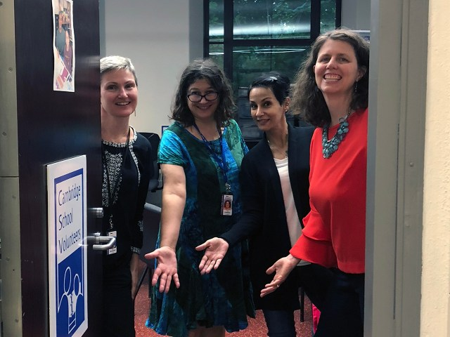 four women in business casual attire in a doorway with hands out welcoming you in to the office